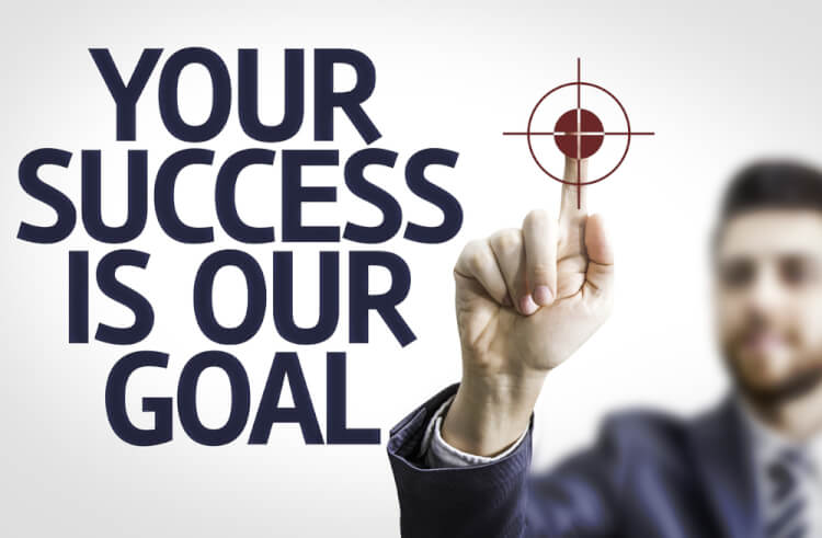 Business man pointing to transparent board with text Your Success Is Our Goal
